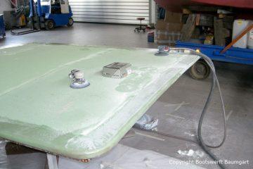 Das Dach der Chris Craft MX 25 Motoryacht wird beim Refit mit Schleifmaschinen für die Lackierung vorbereitet. In der Werfthalle der Bootswerft Baumgart in Dortmund.